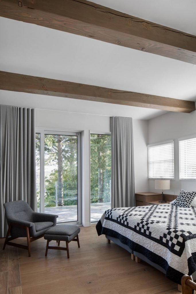 Master bedroom featuring hardwood flooring and white walls, along with a white ceiling with rustic exposed beams.