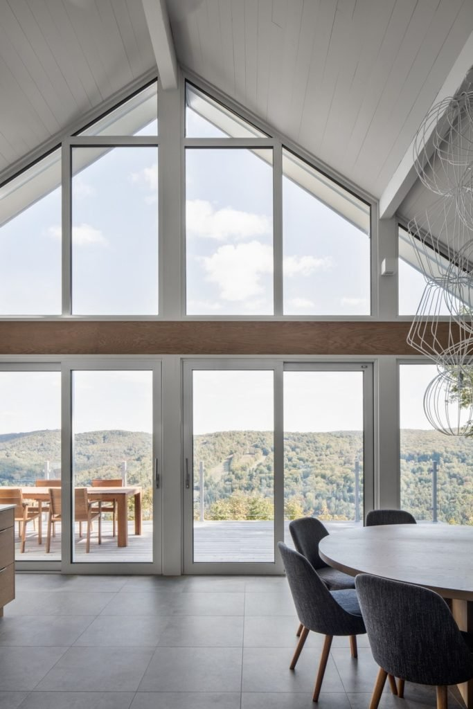 The high vaulted ceiling with tall glass walls makes this home look simply breathtaking.