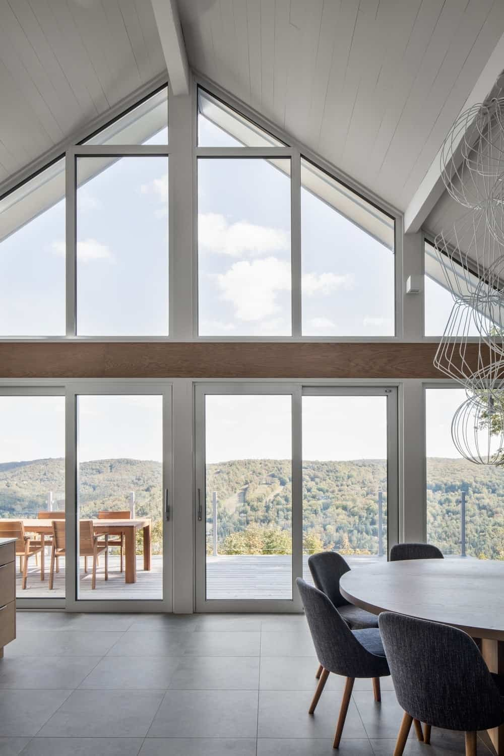 A look at the home's glass windows, walls, and doors leading to the deck patio outside. Photo credit: Adrien Williams