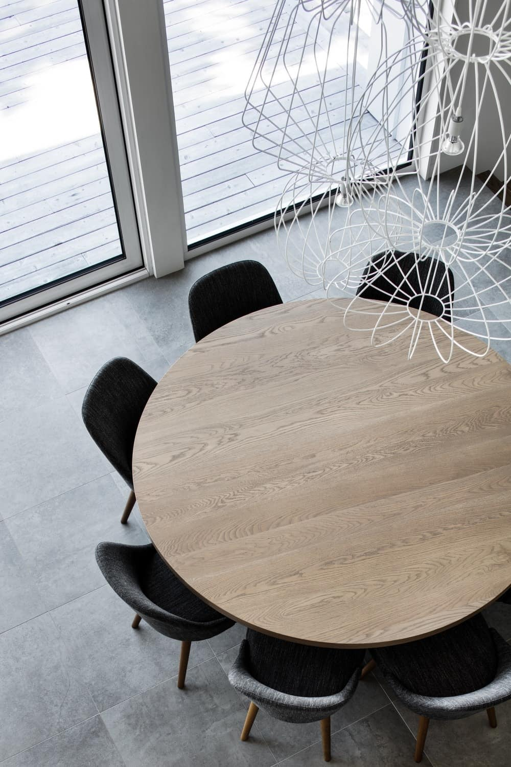 Top view of the dining room focusing on the round wooden table and contemporary chair set. Photo credit: Adrien Williams