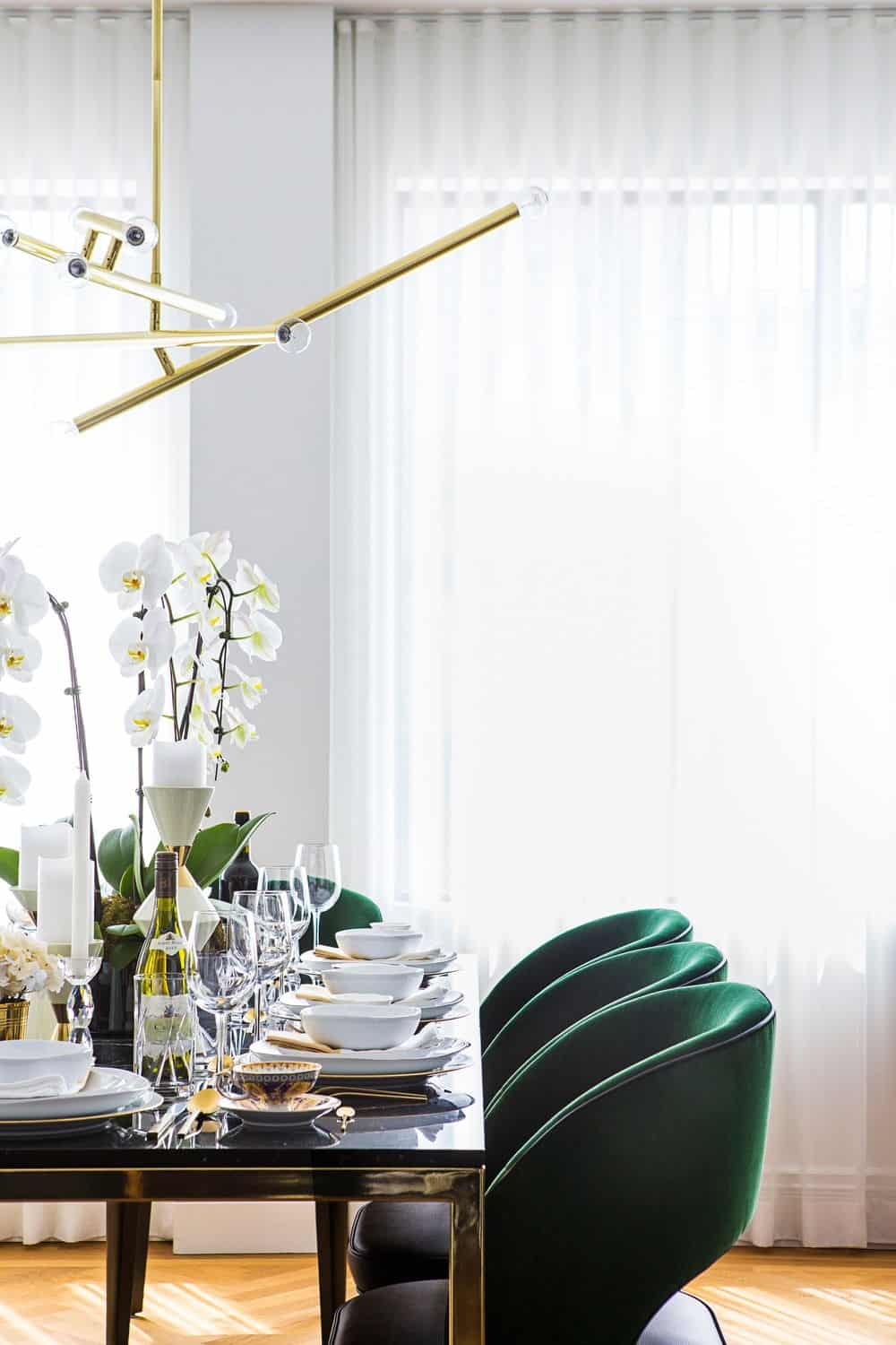 The dining area boasts modish table set and lighted by stylish ceiling light. Photo credit: Erik Rotter