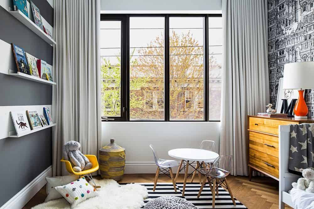 The kids bedroom has built-in shelves and a rug near the glass window protected by white elegant curtains. Photo credit: Erik Rotter