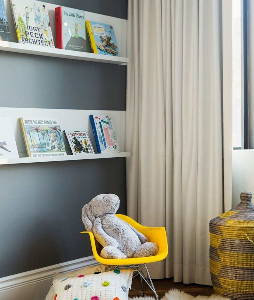Another look of the kids bedroom featuring its fluffy rug, built-in shelves and white curtain. Photo credit: Erik Rotter