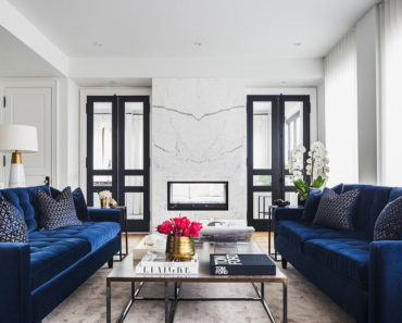 The living room's two beautiful couches, center table and rug surrounded by white walls. Photo credit: Erik Rotter