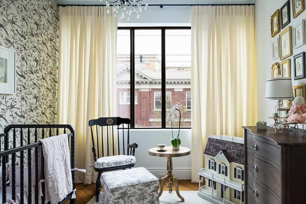 There's also a nursery room with elegant-designed wall and cream-colored curtains along with a chandelier. Photo credit: Erik Rotter