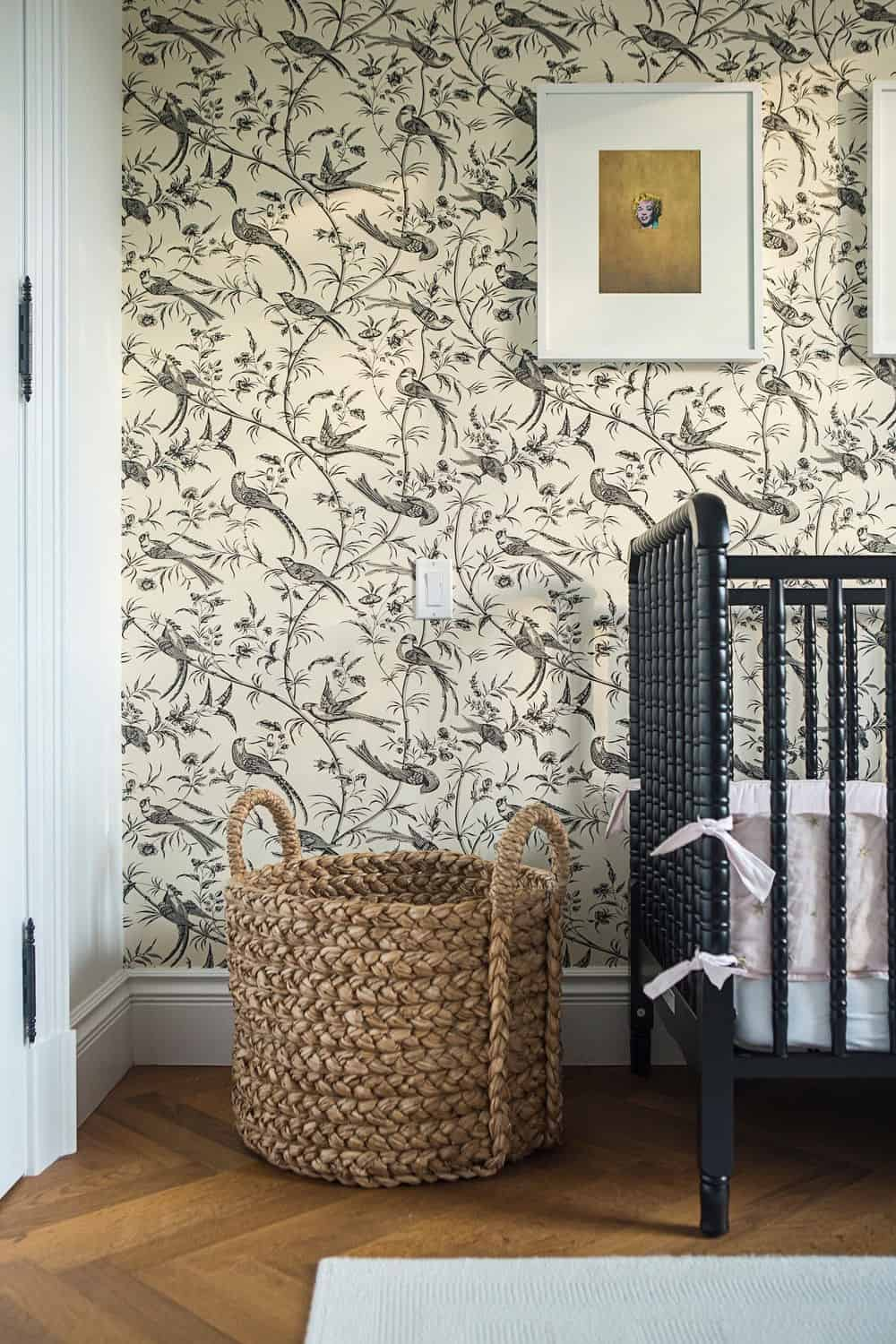 Another look of the nursery room focusing on its beautiful wall and hardwood flooring topped by a rug. Photo credit: Erik Rotter