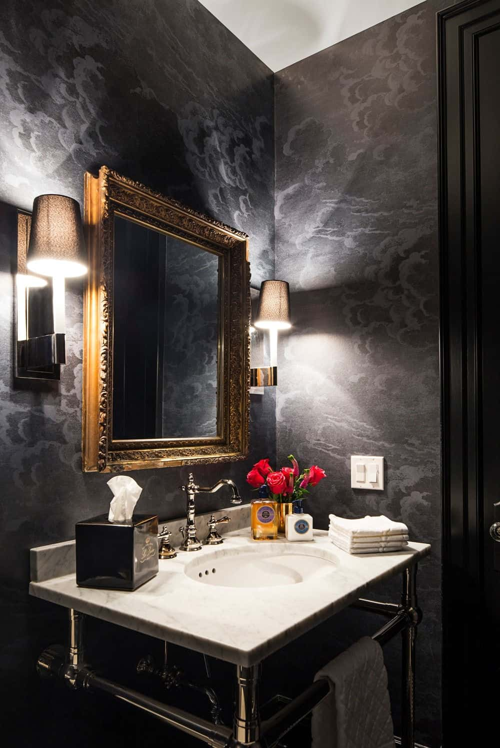 The powder room features a white sink counter surrounded by elegant black walls lighted by a couple of wall lights. Photo credit: Erik Rotter