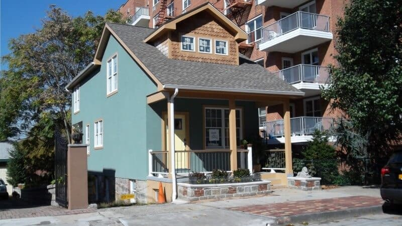 A small and newly renovated house with a green exterior. It has a small porch area as well.