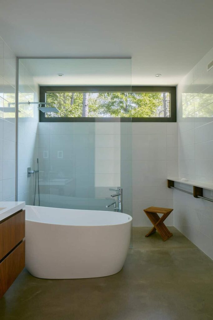 This modern primary bathroom features a stylish flooring, small freestanding tub and an open shower.