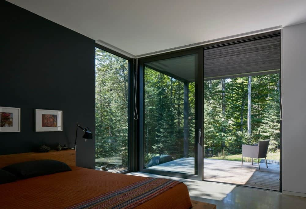Primary bedroom with a beautiful black wall and concrete flooring. It has a glazed door that opens to the patio where you can relax and unwind with the ambiance of the majestic forest.