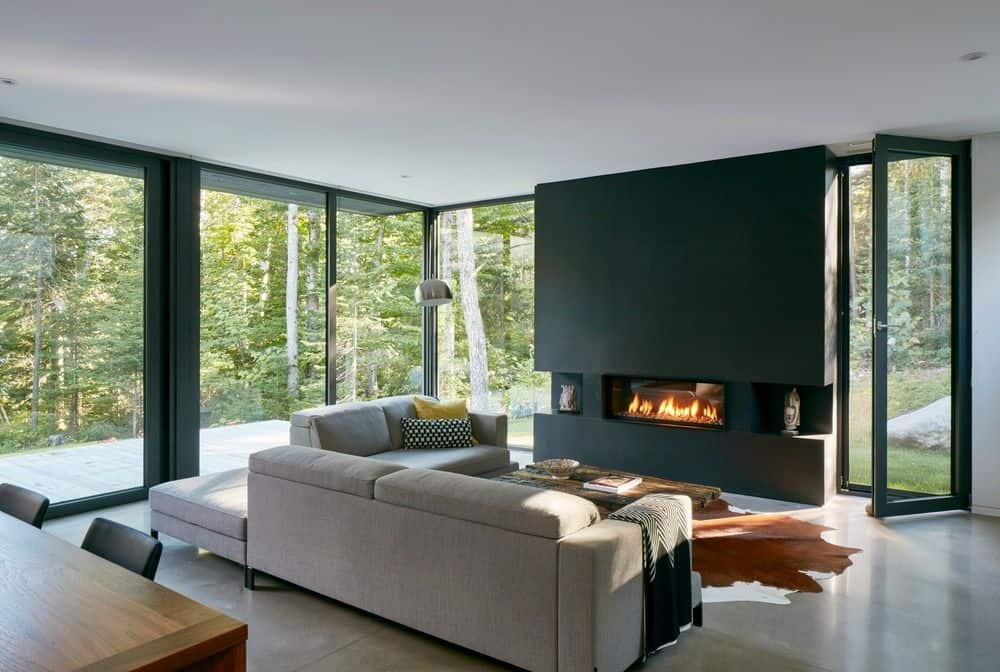 Contemporary style living room with gray sofa set and black fire place. The rustic rug looks beautiful.