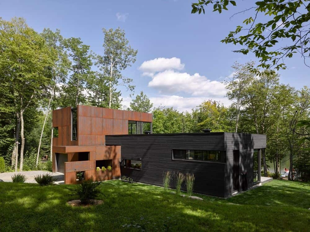 Contemporary house situated on a green lush lawn on the shore of Charlebois Lake. It showcases an L-shape design with a rusty concrete along with dark wood plank.
