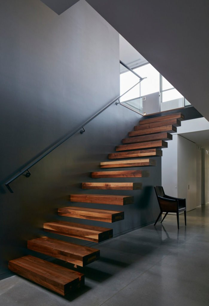 Straight floating staircase with wooden treads and black steel handrail fixed to the gray wall. There's a chair underneath over tiled flooring.
