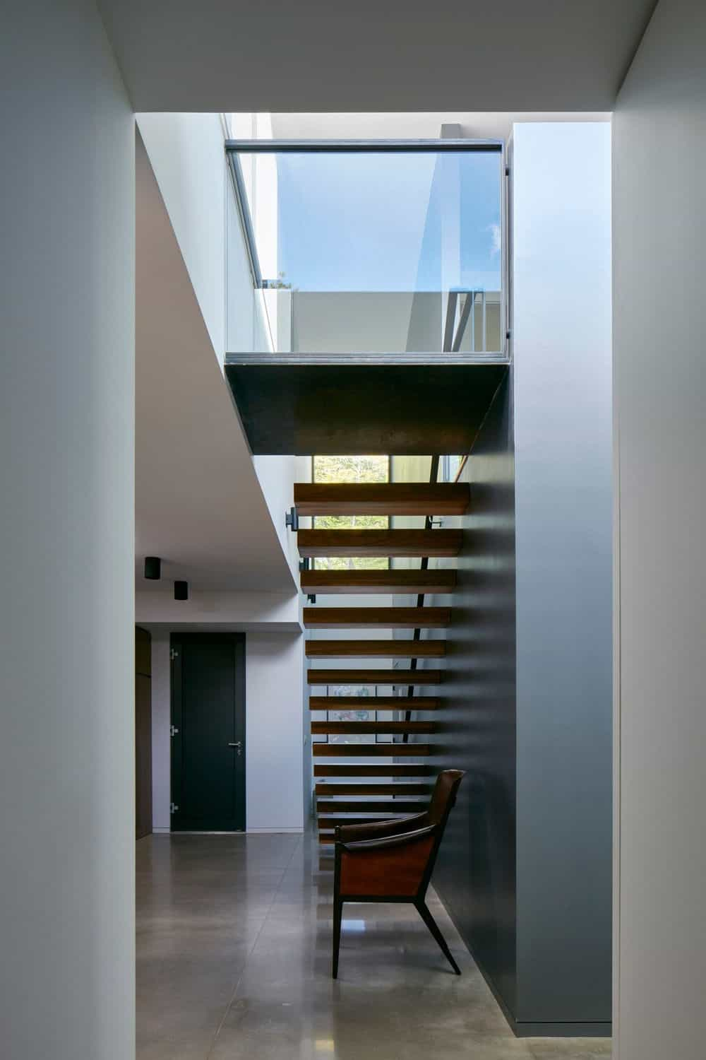 The home features modish walls and floors along with a staircase. Photo Credit: James Brittain