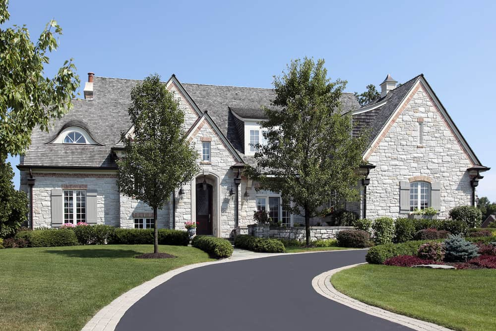 Very smart asphalt driveway concept here with the light gray brick border that matches the light stonework of the home.