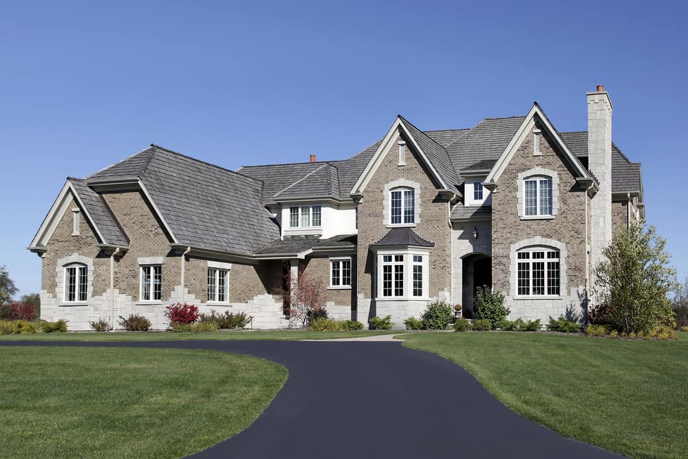 Large suburban mansion with new asphalt circular driveway amidst extensive green lawn.