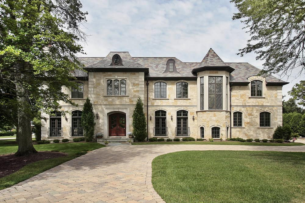 Elegant mansion with long brick circular driveway that circles by the front of the home and extends behind the home to the garage.