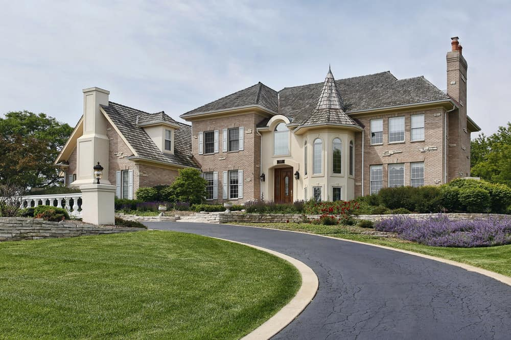Large McMansion on a hill with asphalt circular driveway winding through the front of the property.