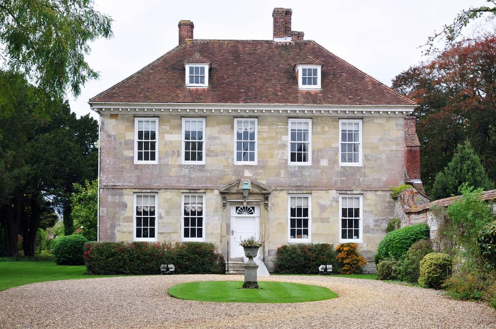 Old manor home with round gravel driveway with fountain in the center.
