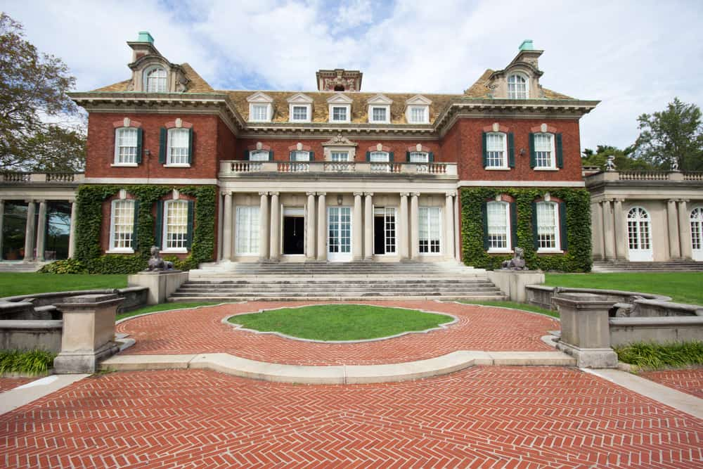 Old Gold Coast red-brick and ivy covered mansion with round red brick front walkway.
