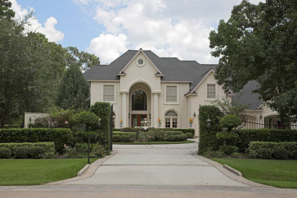 Mansion set back from the road accessed via concrete and brick driveway that enters through gates and ends with a full circle. Hedge bushes and flowers planted in the middle of the circle which makes for a beautiful entrance to this property.