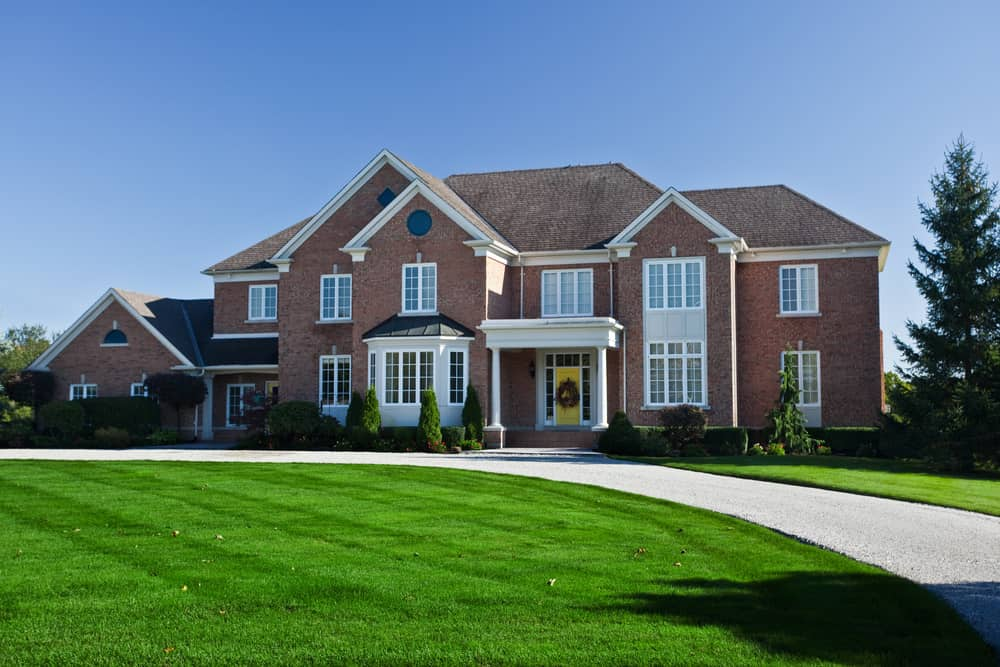 Large red brick mansion with gray gravel circular driveway amidst huge green lawn.