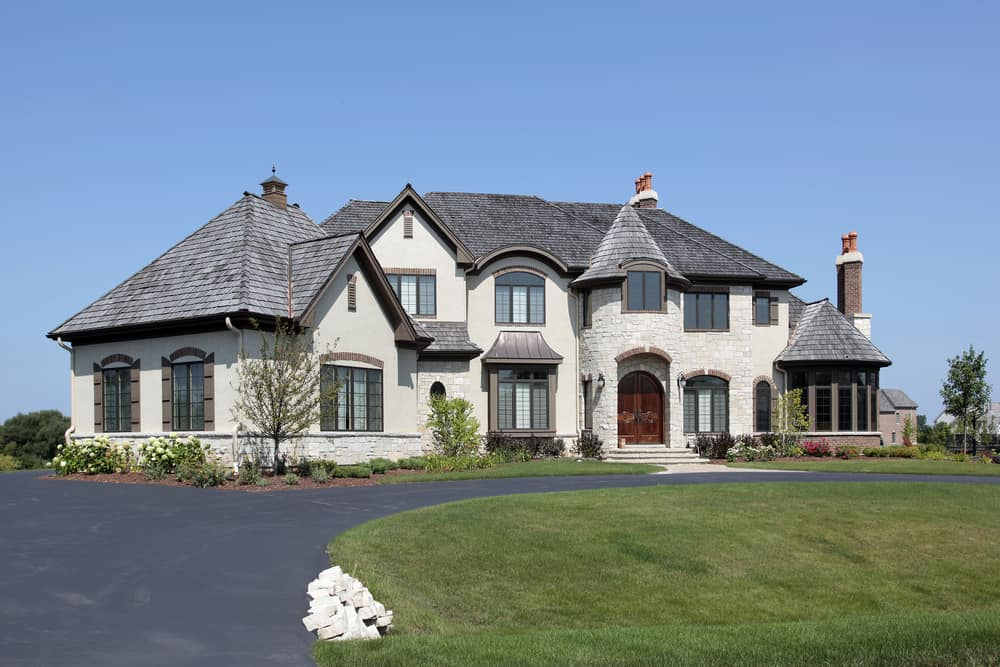 Large home with plain dark asphalt driveway in a u-shape design.