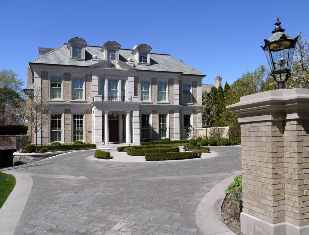 Elegant and ornate mansion with circular grey brick driveway bordered with lighter gray concrete perimeter.