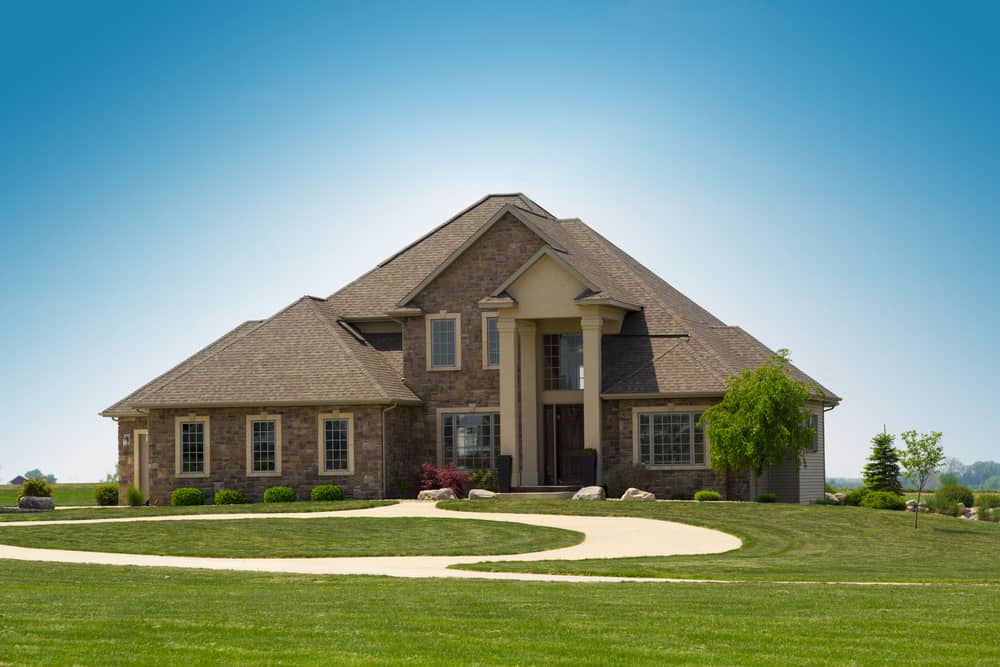 New house on huge property with full circular beige driveway in front of the home.