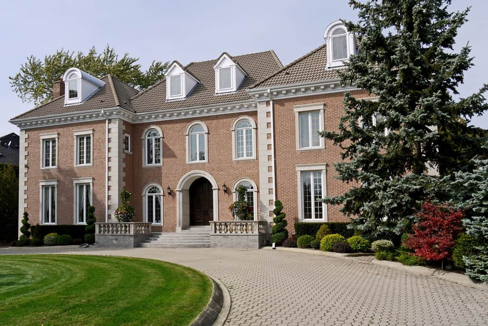 Stately red brick mansion with u-shaped circular brick driveway.