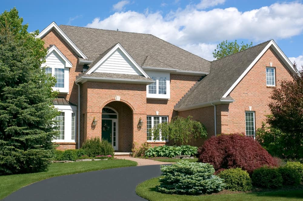 Stately red brick home with new asphalt u-shaped driveway.