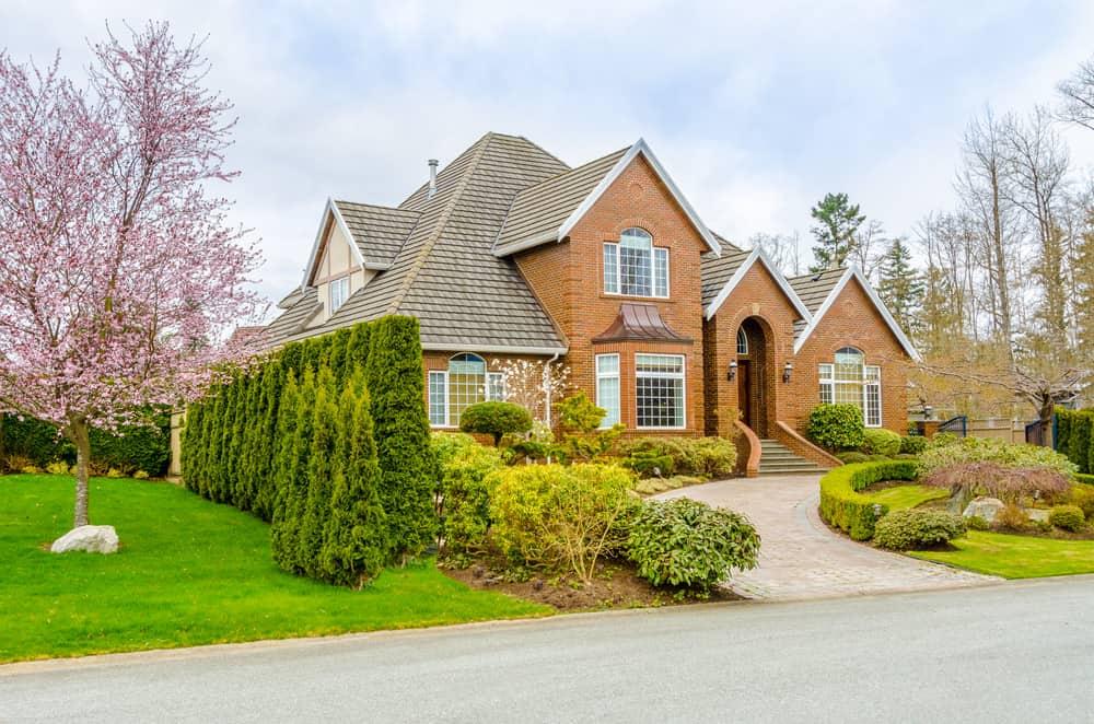 Red brick large suburban home with u-shaped brick driveway.