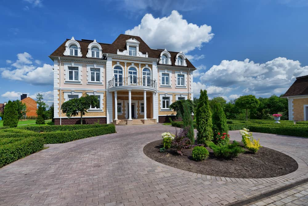 Elegant and ornate three story mansion with circular brick driveway with garden in the center and bordered with boxwood hedge.