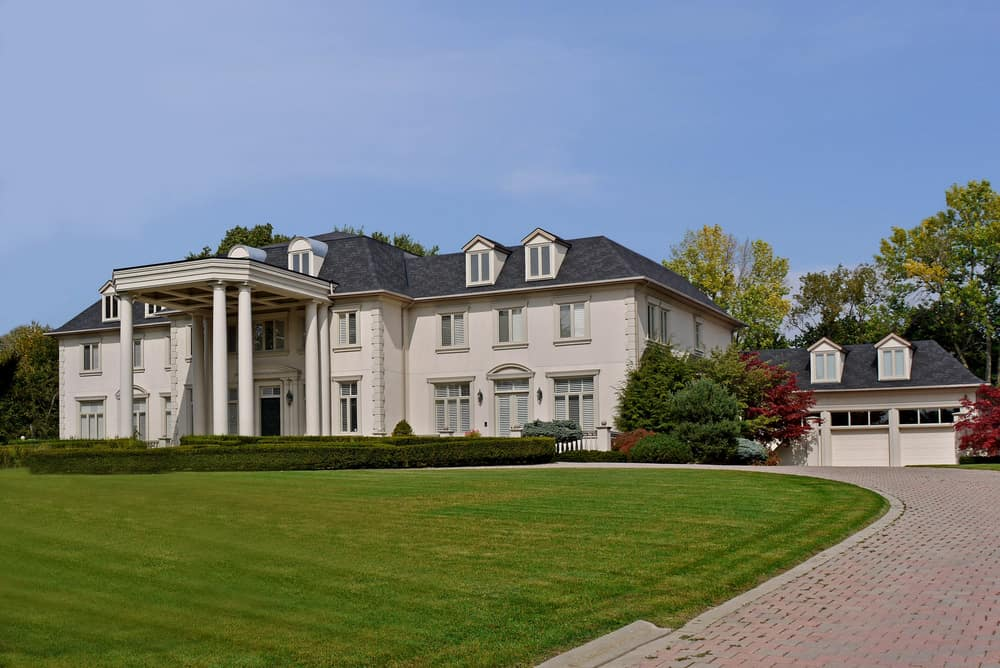 Grand mansion with huge two-story portico with brick driveway leading up to the front entrance and winding through the portico down to the opposite end of the large property. Just imagine what this lengthy driveway cost to build.