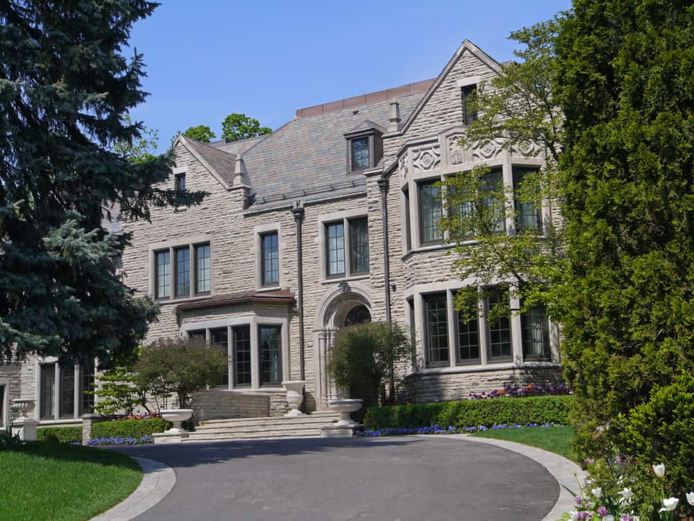 Close up of grey stone mansion with asphalt cicular driveway nicely bordered with gray pavers.