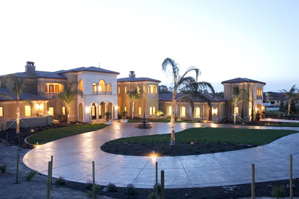 Large contemporary Tuscan style villa home with circular stamped concrete driveway.