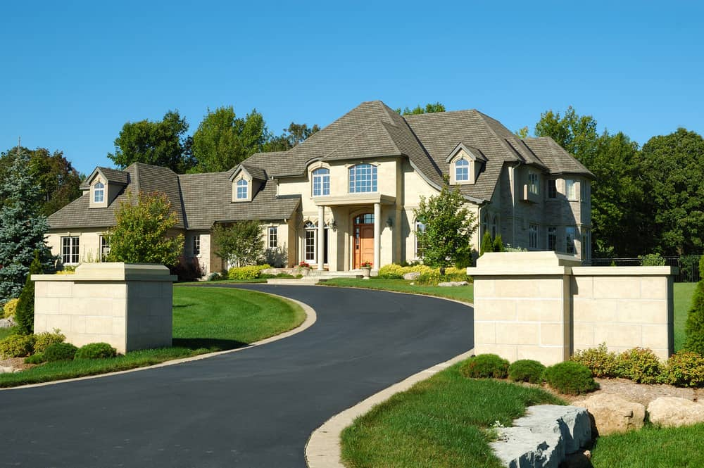New mansion in suburb with asphalt drive bordered with beige bricks.