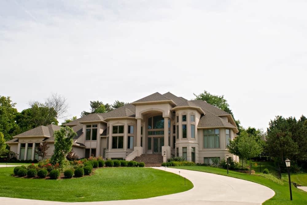 Imposing contemporary mansion with light beige circular driveway.