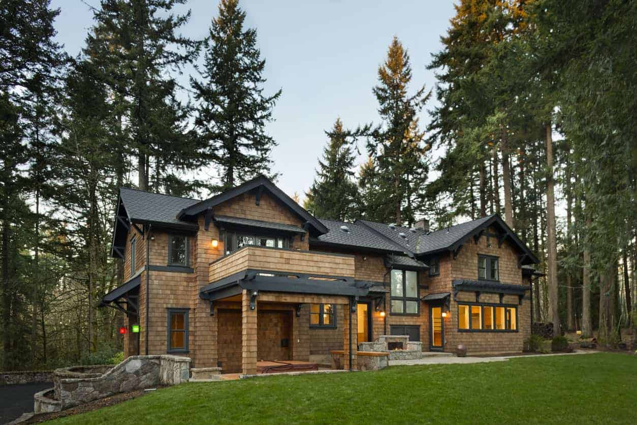 Large shingle exterior home with dark gray trim and dark gray roof shingles. It has a dark appearance, but there's sufficient contrast to make it a beautiful exterior.