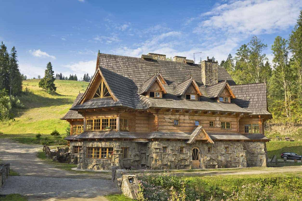 Grand three story wood exterior mansion set on large country property. Arguably this is a log home - hewn logs... but we included it here because it has more of a natural wood siding look than log exterior look. Besides, it's so cool, it would enhance both our log home gallery and this gallery.