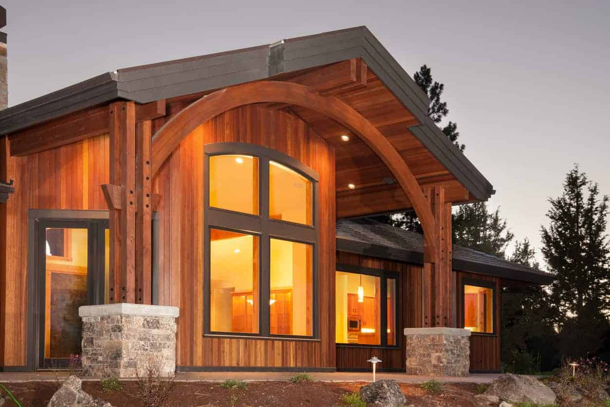 Close up of a new home with vertical wood board home exterior that includes the same wood for support columns. The contrast is created with dark gray trim. while it's a lot of wood (rich red wood at that), it works.