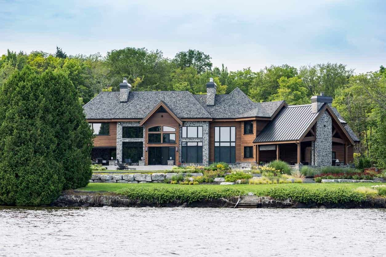 Luxurious lakefront property located in Lac St-Joseph, a rich suburb of Quebec City. This mansion has plenty of natural wood on the exterior as well as gray stonework that matches the color of the roof shingles. It creates a beautiful curb appeal.