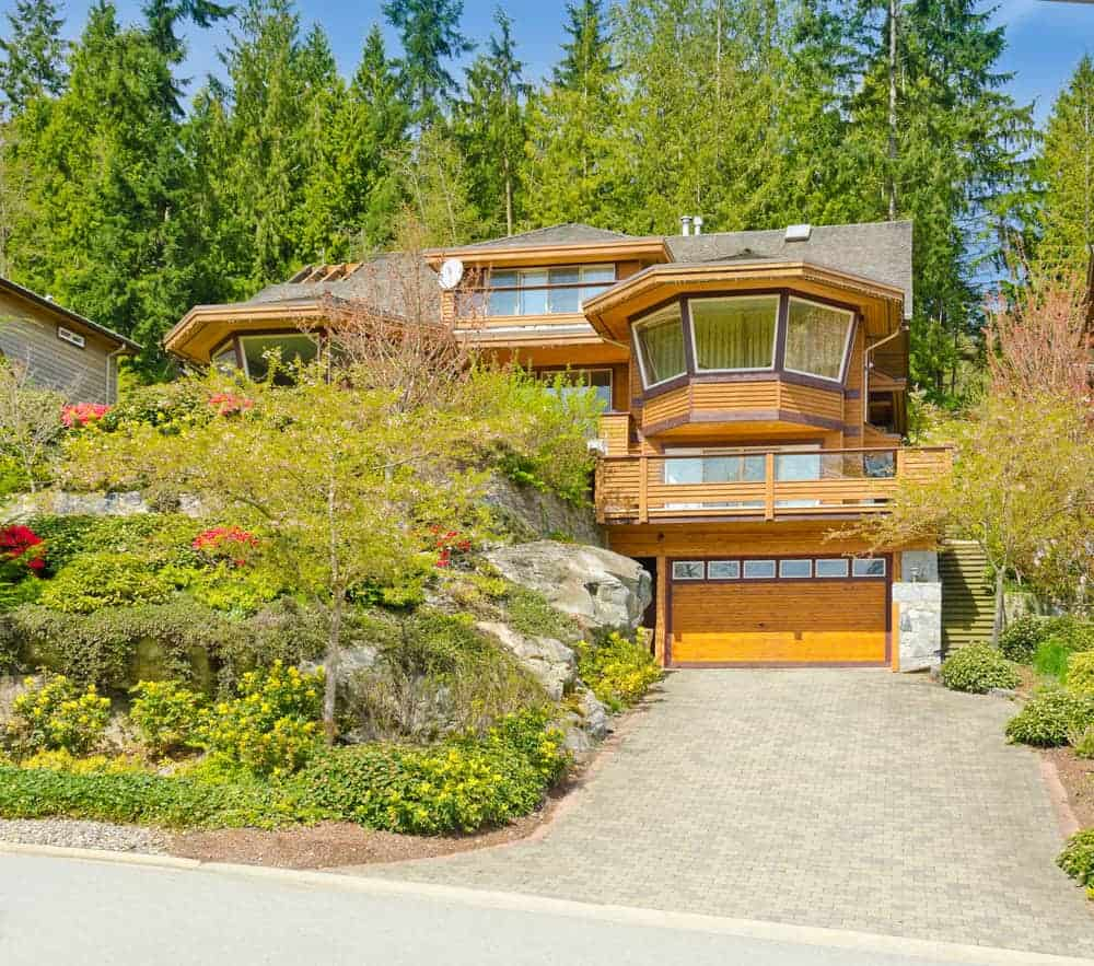Mountain-side home with extensive wood exterior - light with dark brown wood trim.