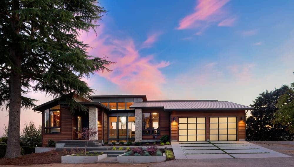 Contemporary ranch style home with medium dark natural wood exterior combined with some gray stone. The translucent garage doors create a stunning effect along with the large floor-to-ceiling windows. I love the style of this home.