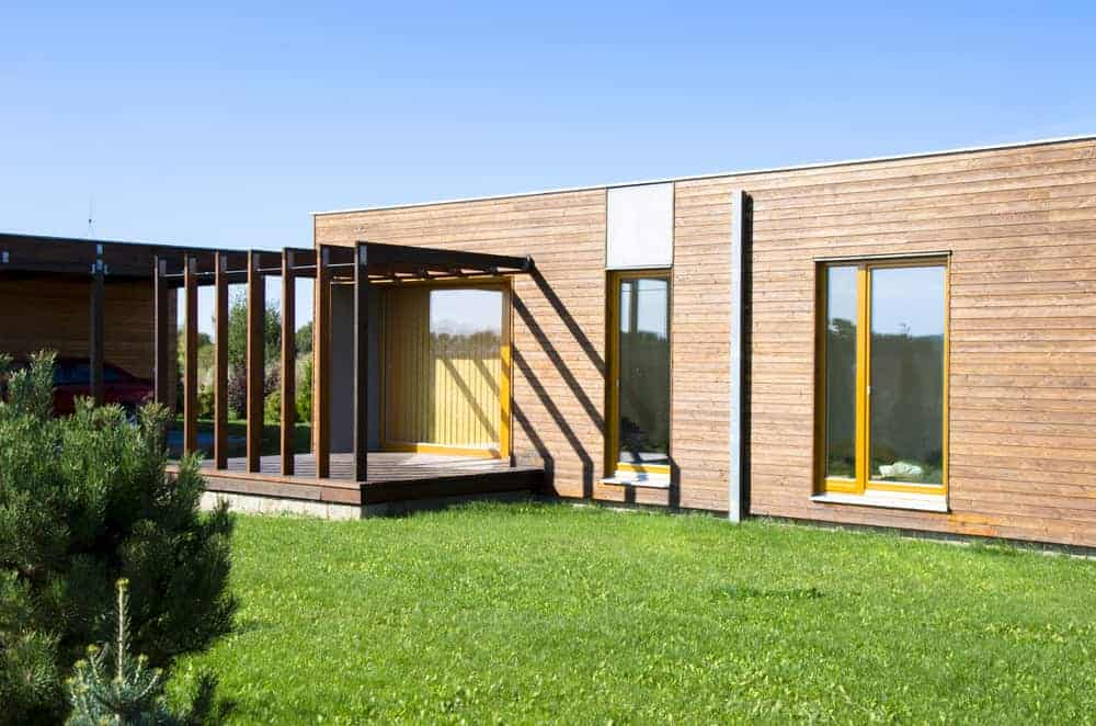 Modern flat roofed-home with horizontal wood board exterior from base to roof.