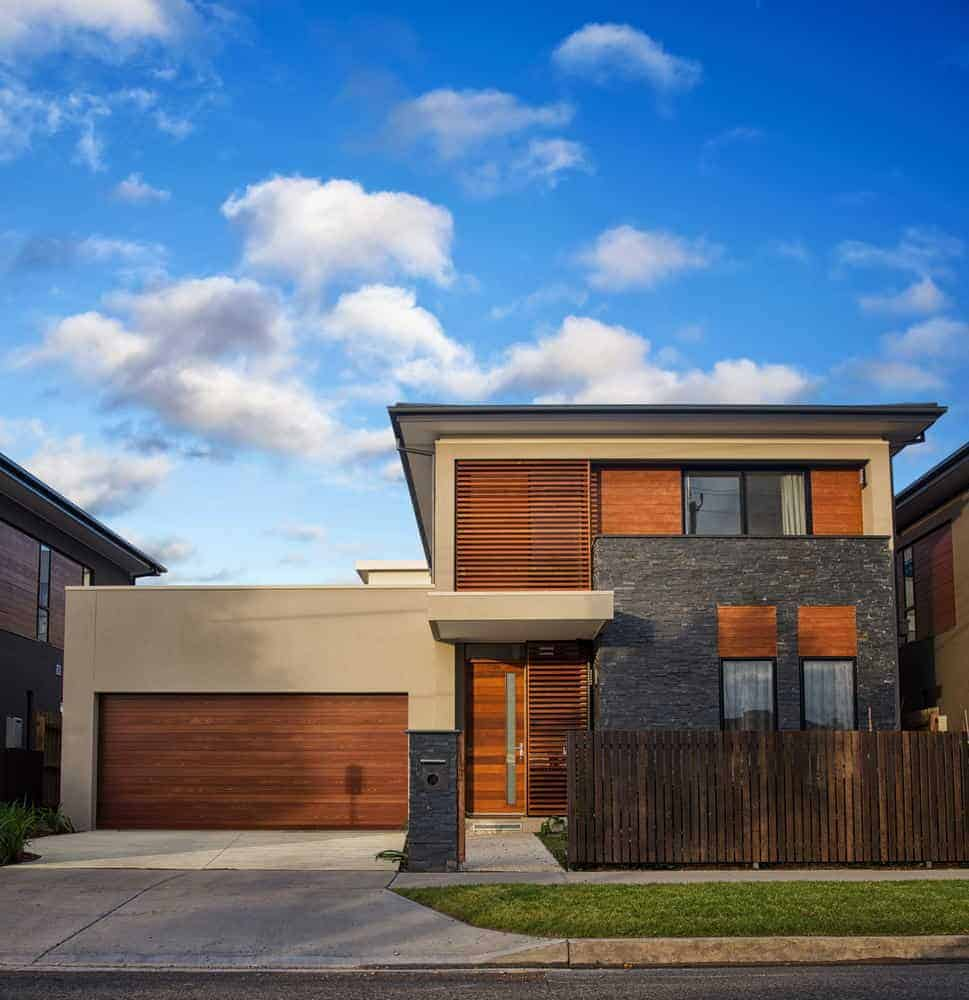 Interesting urban home with slat wood exterior as well as a natural wood garage door. Includes stucco exterior as well creating contrast in color and texture.