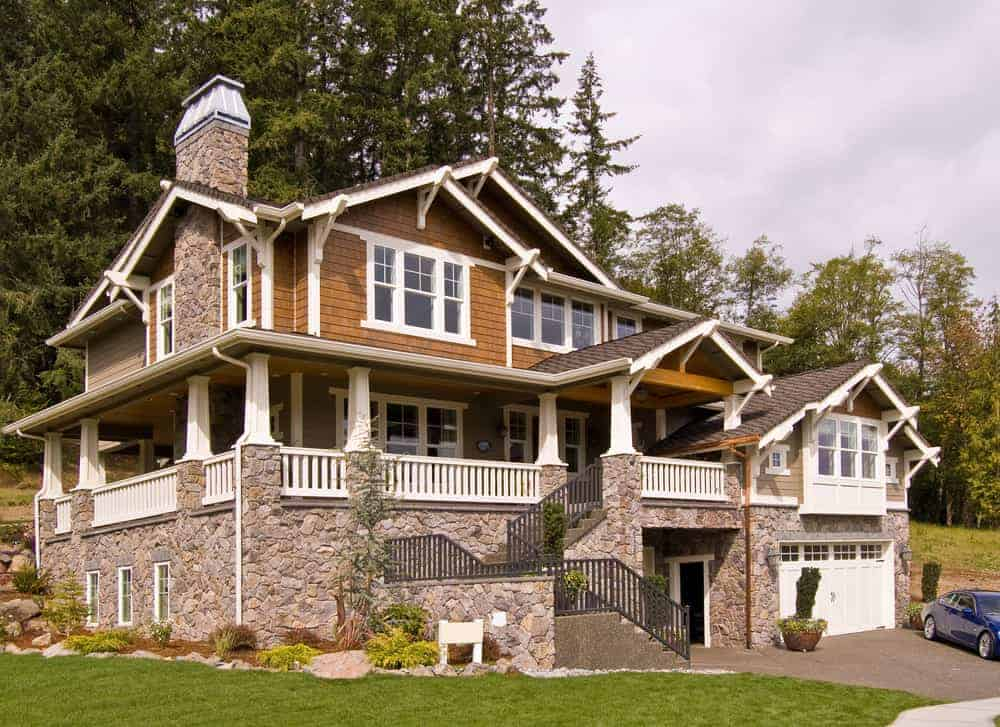 Large hillside home with natural wood siding combined with stone with white trim. It's an imposing home especially as it's built up on a robust stone foundation.