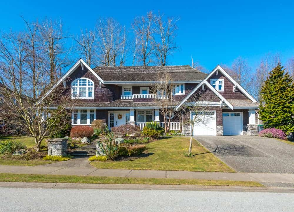 Elegant dark shingle style exterior with white trim on wide suburban property. The shingle exterior matches the roof shingles. It's a good thing there's plenty of white trim to avoid a gloomy looking exterior.