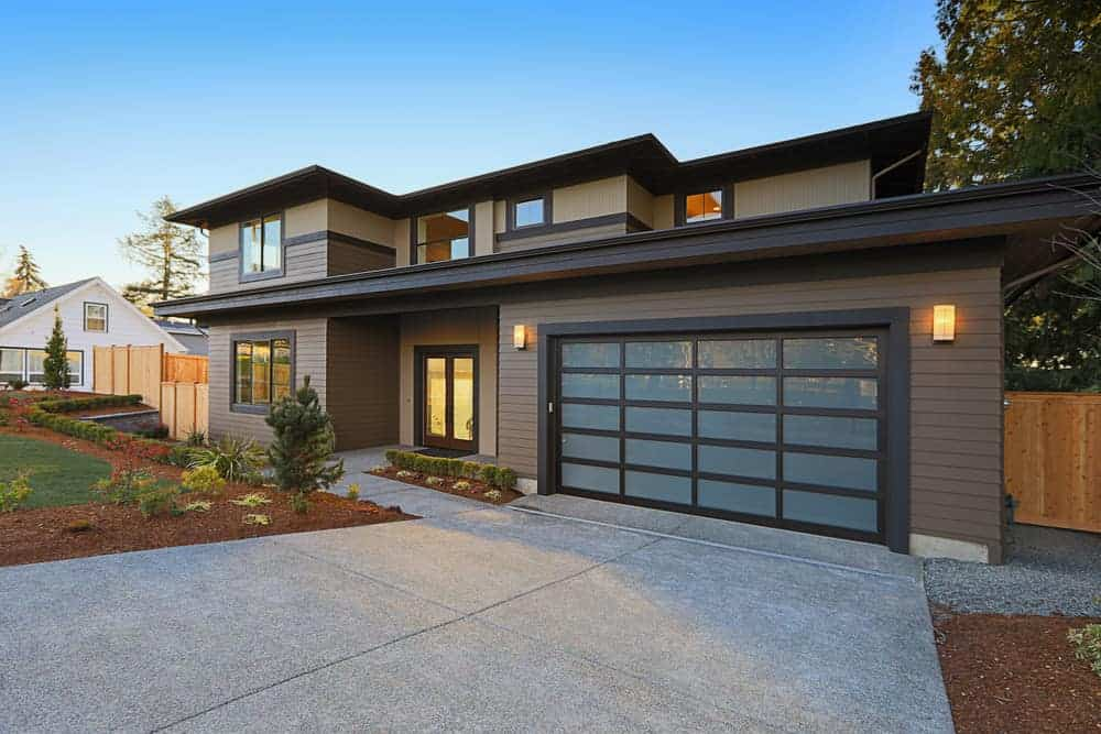 Suburb home with dark wood exterior and translucent garage door. It has a modern vibe but still leans toward a traditional style.