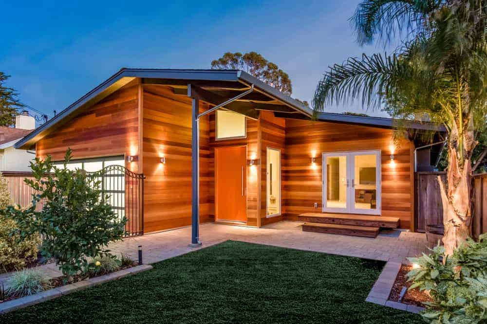 Small renovated home with beautiful light and medium dark horizontally oriented wood board exterior.